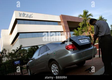 Un guardia de seguridad comprueba un coche con explosivos en una de las puertas de entrada a la sede de Infosys en Bangalore en la India Foto de stock