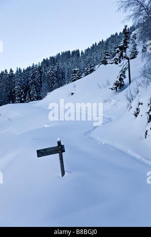 Cartel de madera con el camino cubierto de nieve en la estación de Les Alpes Franceses Saises
