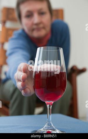 Una mujer madura solo en necesidad de beber sentado llegar a recoger una copa de vino tinto en una tabla en la parte delantera. Inglaterra Gran Bretaña