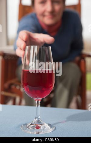 Una mujer madura de la generación del baby boom sentarse llegar a recoger una copa de vino tinto en una tabla en la parte delantera. Inglaterra Gran Bretaña