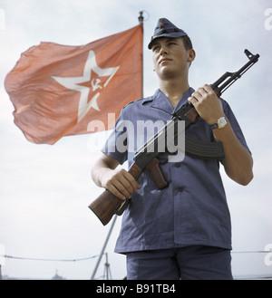 Un marinero en un uniforme tropical de guardia cerca de un buque de guerra de bandera Foto de stock