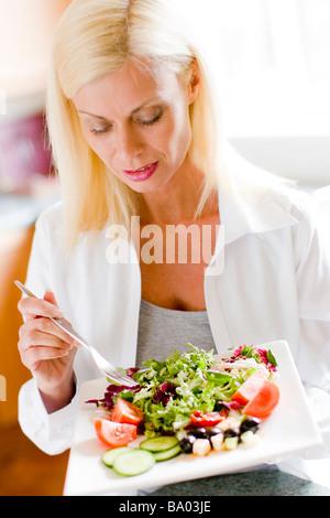 Retrato de mujer madura comer ensalada