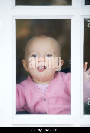 BABY GIRL,10 meses, mirando por la ventana, sonriente y lengua fuera