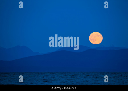 Luna llena ascendiendo por encima de las montañas de la costa de la Columbia Británica continental visto desde Fillongley Foto de stock