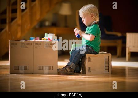 Niño jugando con juguetes en cajas de cartón