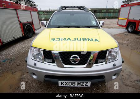 Paramédico ambulancia respuesta rápida con el coche de bomberos en segundo plano.