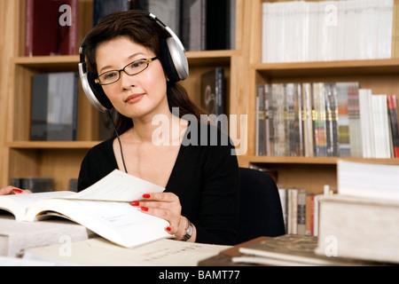 Mujer vistiendo los auriculares mientras estudiaba