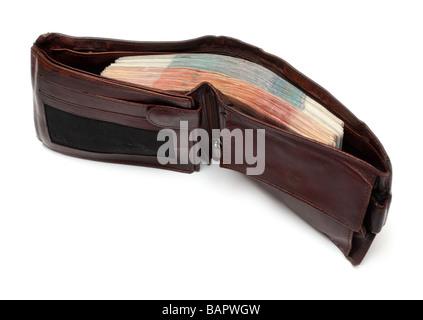 Bolso marrón con gruesos lote de billetes aislado en blanco