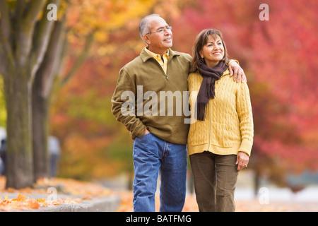 Pareja de hispanos caminando afuera en otoño