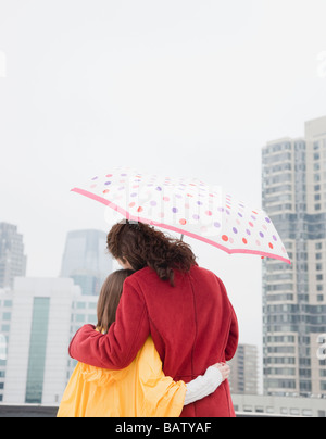 Ee.Uu., la ciudad de Nueva York, madre e hija (10-11 años), abrazando bajo la sombrilla, vista trasera