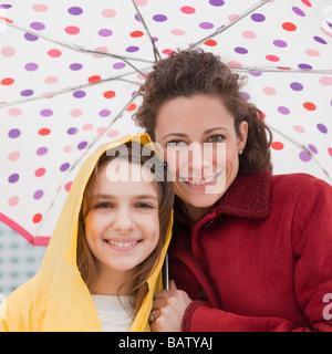 Madre e hija (10-11 años) bajo un paraguas, Retrato