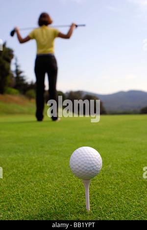 Mujer joven golfista del terreno y de las condiciones de observación antes de golpear
