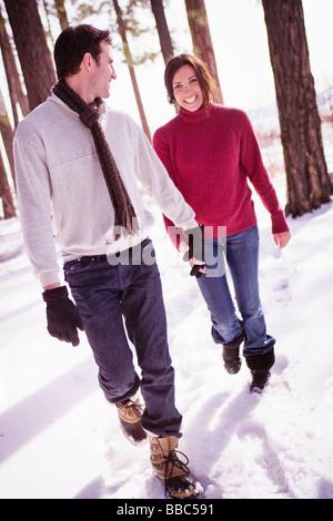 Par caminando a través del bosque cubierto de nieve Foto de stock