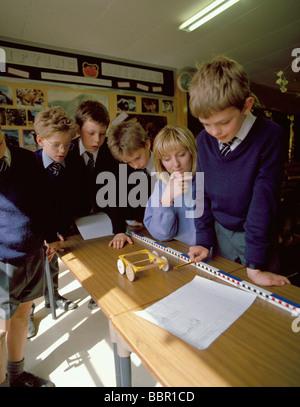 Los estudiantes midiendo la distancia recorrida por un buggy en una lección de física.