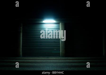 Oscuro pasillo con tienda urbano cerrado por la noche