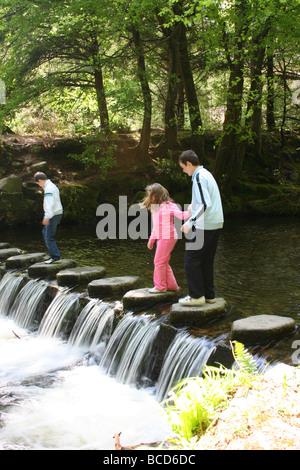 Niños jugando en el Stepping Stones sobre el río Shimna Tollymore Park, Condado de Down, Irlanda del Norte
