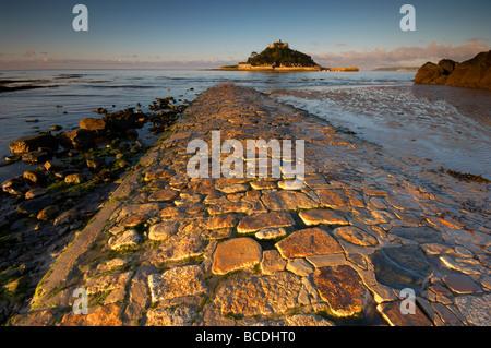 Amanecer sobre la antigua calzada de piedra conduce a St Michaels Mount en la costa de Cornualles UK