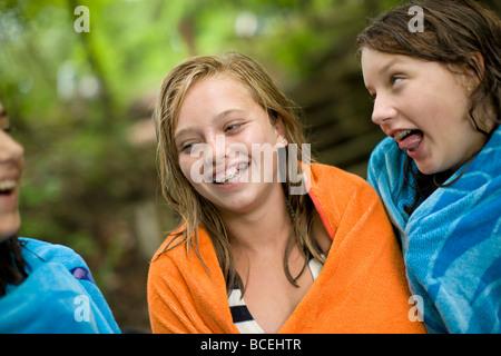 Las adolescentes están riendo y divirtiéndose mientras envuelto en toallas de playa