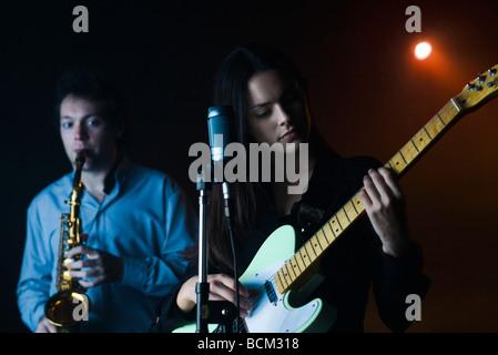 Los jóvenes músicos tocando la guitarra eléctrica y el saxofón en el night club