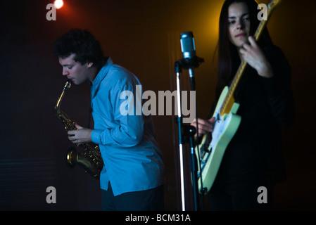 Los jóvenes músicos tocando el saxofón y guitarra eléctrica en night club