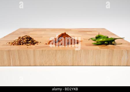 Selección de tipos de chiles secos, frescos y en polvo, sobre una tabla de cortar de madera contra el fondo blanco. Foto de stock