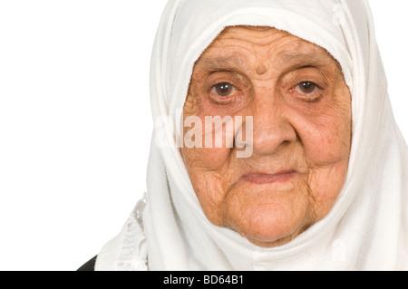 Cerca de una vieja mujer contra un fondo blanco. Foto de stock