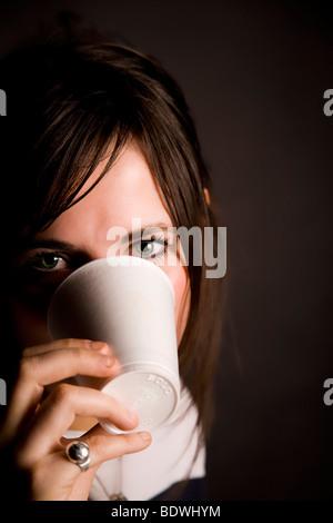 """Hermosa joven """"ocultar"""" detrás de una taza de poliestireno."""