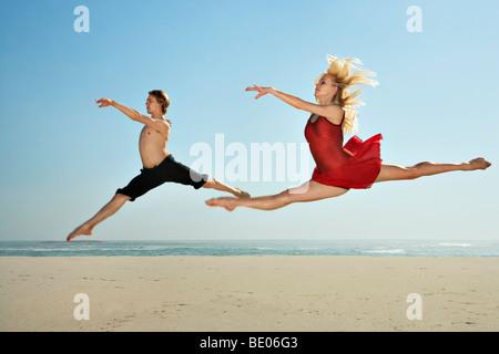 Los bailarines saltando en una playa Foto de stock