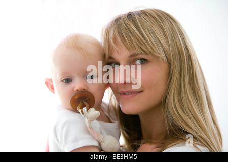 Un año de edad en el brazo a su madre.