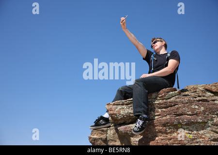 Joven tomando el autorretrato en la parte superior del acantilado Foto de stock