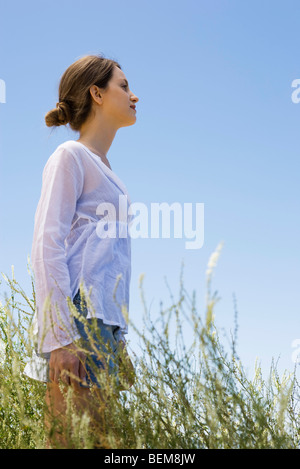 Mujer joven de pie en el pasto alto, vista lateral