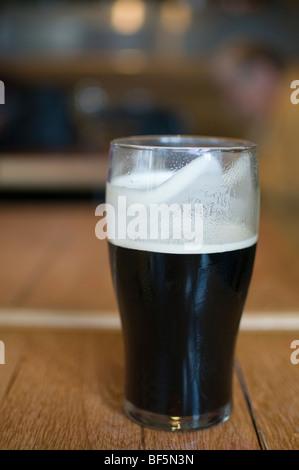 Una pinta de cerveza negra real ale sentado en una mesa de pub