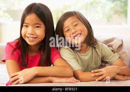 Dos niñas relajándose en el sofá en casa Foto de stock