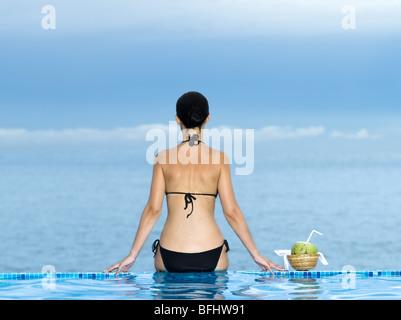 Mujer siiting en el borde de una piscina con vista al mar Foto de stock