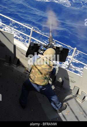 Compañero de artilleros disparando una ametralladora calibre .50 a bordo del crucero de misiles guiados USS Vella Gulf.