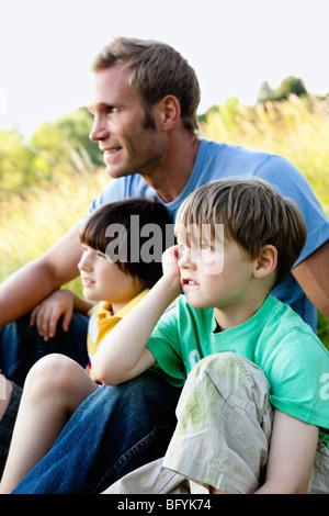 Los muchachos y el padre sentado en prados