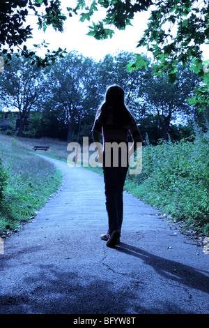 Vista trasera de un joven caminando por un parque o un área del país