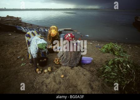 Tres mujeres separados mangos en depósitos en el banco del río Níger en Segou Malí África Occidental como se acerca una tormenta