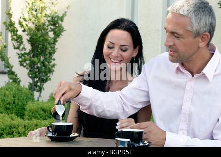 Pareja Sentada detrás de la mesa de café. El hombre vierte la leche en el café Foto de stock