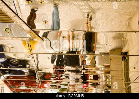 Refleja y distorsiona las cifras en un techo espejo en el interior de la entrada del hotel Praga Foto de stock