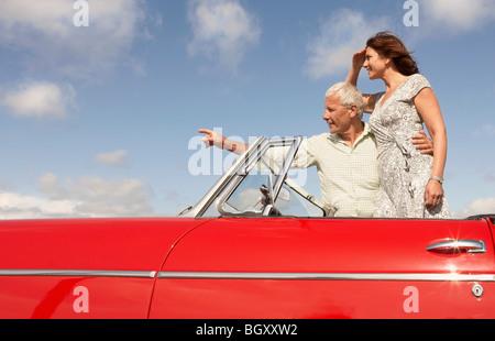 Las parejas ancianas en coche deportivo, apuntando