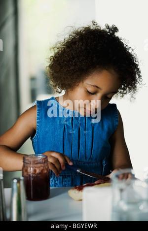 Pequena chica preparar merienda de pan y mermelada