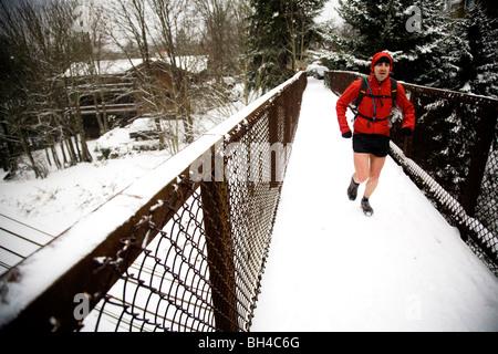 Un hombre con una mochila runner corre a través de un puente cubierto de nieve, mientras que en pantalones cortos en el invierno.