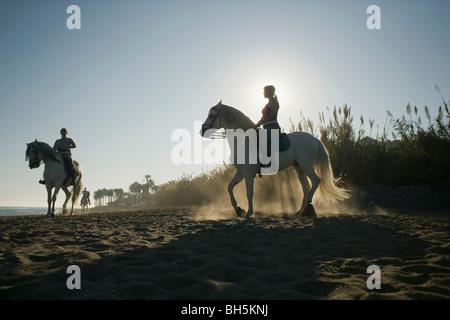 Tres mujeres a caballo en la playa