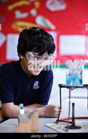 Adolescente en la escuela clase de ciencias , Reino Unido, el uso de las gafas de seguridad, viendo el experimento