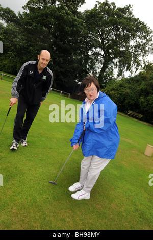 Dos mujeres con discapacidades de aprendizaje jugar pitch and putt, North Yorkshire
