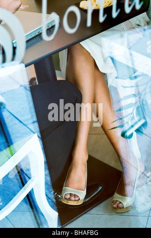 La mujer joven tocando la pierna bajo la mesa del joven