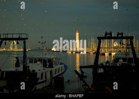 En Sète, Francia, el mayor puerto pesquero del Mediterráneo, los arrastreros están amarrados tranquilamente como el sol vespertino ilumina el faro