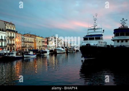 En Sète. Francia, el mayor puerto pesquero del Mediterráneo, los edificios brillan al atardecer junto a los arrastreros amarrados en el Royal Canal