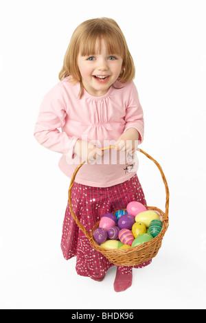Niña llevar cesta llena de huevos de Pascua